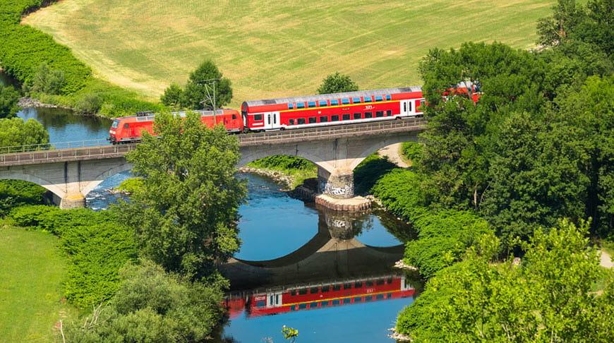 Европейский поезд едет через реку и красивые луга